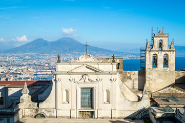 Bright skyline view of Naples, Italy with Mount Vesuvius standing above a cityscape dominated by an old church in the foreground