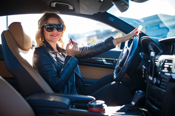 Photo of happy blonde in black glasses paints lips sitting in car