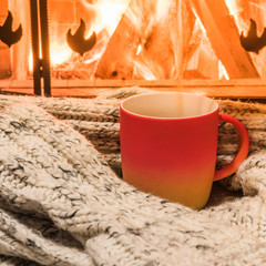Cozy scene near fireplace with a Red cup of hot tea and cozy warm scarf.