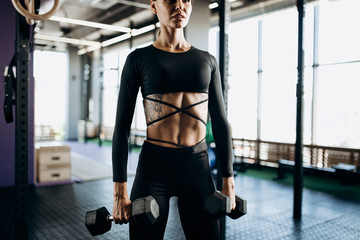 Slender young woman with tattoo dressed in a black sportswear is doing exercises with dumbbells in the gym