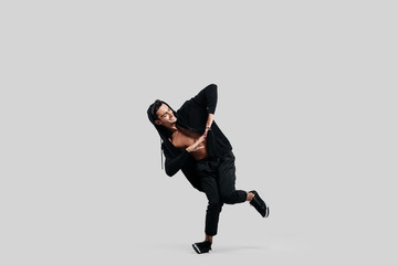 Young handsome young dancer dressed in black pants, a sweatshirt on a naked torso is dancing street dance. He makes stylized movements with his hands