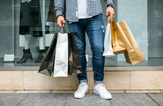 Low section of unrecognizable young man shopping with paper bags in his hand