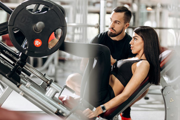 Slender girl dressed in black sport clothes is lifting weights with her legs in the gym under the supervision of a coach