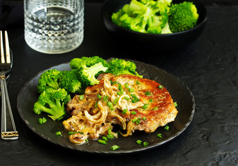 Fried pork steak with broccoli and onion sauce.