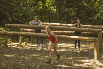 Fit women training over obstacle course