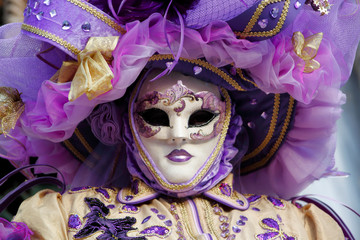 Carnival purple-beige-gold mask and costume at the traditional festival in Venice, Italy
