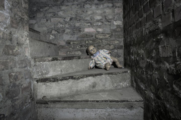 Scary demonic doll sitting on the steps in the basement Fototapete