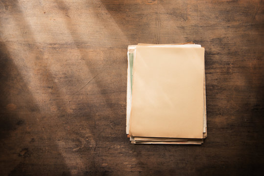 Old documents in blank on a old wooden desk, with by the window type light coming in. Ready for inserting your message or text.