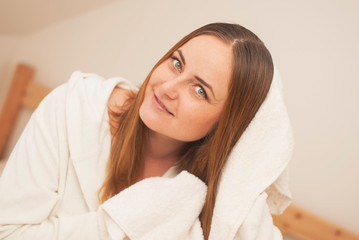 Lovely female with wet hair, dries head with towel, being pleased after taking bath, dressed in white bathrobe, poses against white background