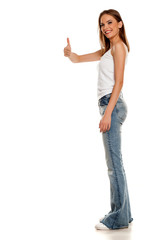 happy young pretty woman posing in bell bottom jeans on white background and showing thumbs up