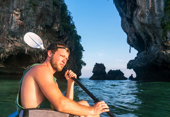 Kayaking around hight amazing Limestone Rocks at Railey Beach in Krabi, Thailand.