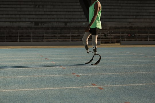 Low section of disabled athlete standing on running track