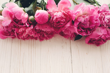 lovely pink peonies border  in light on rustic white wooden background top view, space for text. floral greeting card mock-up. happy mothers day concept. beautiful spring image