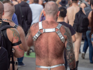 Rear view of hairy man wearing silver BDSM harness and thong walking in crowd