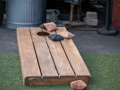 Sets of beanbags in competitive game of cornhole on a lumber platform