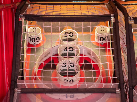 Scoring area of skee ball game behind a net with values of 10 to 100