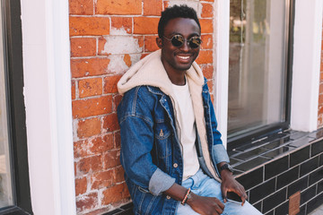 Wall Mural - Fashion smiling african man in jeans jacket sits on city street, brick wall background