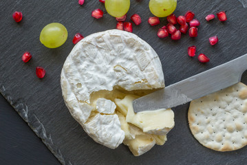 Camembert cheese top view photo on slate cheese board