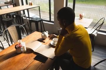 Woman looking at menu in cafe
