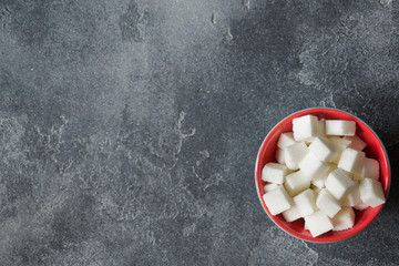 White sugar cubes in a plate on a dark brutal background Selective focus