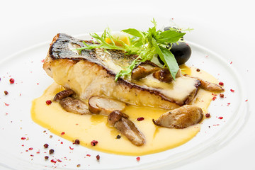 Pike perch with porcini mushrooms and potatoes. On a white plate