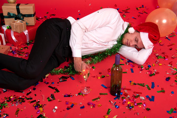 Young businessman hangover sleeping after drinking of alcohol in office. christmas and happy new year party.