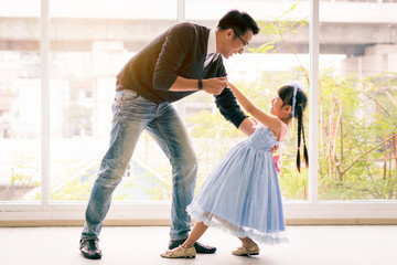 Cute little girl is dancing with her daddy. Having fun at home together concept