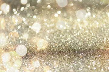 Gold and silver abstract bokeh lights. Shiny glitter background with copy space. New year and Christmas concept. Sparkling greeting card