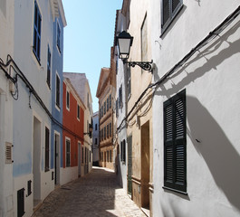 A bright sunlit narrow empty town street of picturesque old houses in Ciutadella menorca