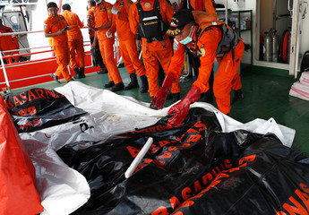 Search and rescue workers lay out body bags and bags of debris on a vessel at a search area in Karawang waters