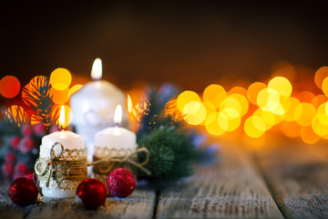 Merry Christmas and happy New year. Candle and Christmas toys on a wooden table on the background of a garland. Bokeh. Selective focus. Background with copy space.