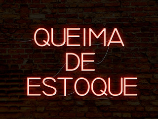 Clearance Sale (in portuguese) red neon sign. Background texture of rustic brick wall old red orange