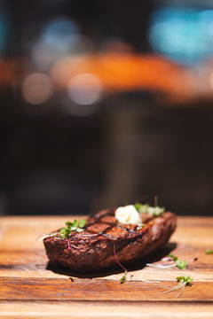 piece of beef steak on wooden plate with bokeh background