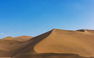 Desert sand dunes with blue sky background. Beautiful curves of deserts