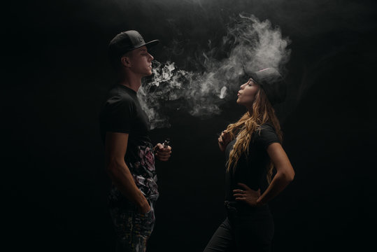 Couple vaping. Young man and woman blowing smoke to join it in one cloud at black studio background. Relationship and vape addiction concept with copy space