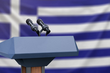 Podium lectern with two microphones and Greek flag in background