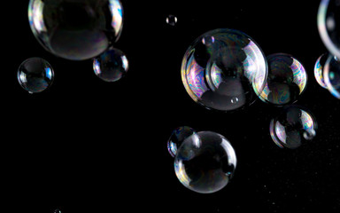 Multicolored soap bubbles close up on a black background, similar to planets