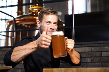 Obraz Piwo. Uśmiechnięty przystojny mężczyzna z kuflem piwa pszenicznego. - fototapety do salonu