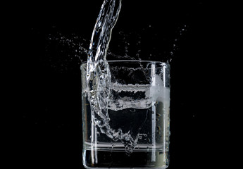 Bounce and splash from a piece of ice thrown into a transparent glass with water on a black background