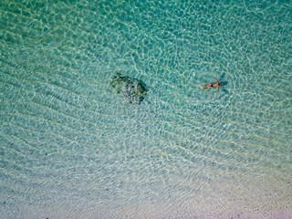 Indonesia, Bali, Melasti, Aerial view of Karma Kandara beach, man swimming