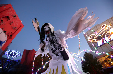 A participant in costume poses for a photo during a Halloween event in Beijing