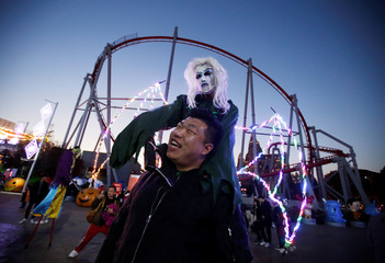 A participant in costume poses for a photo with a visitor during a Halloween event in Beijing
