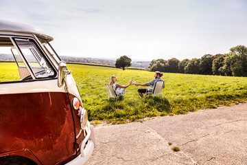 Couple on camping chairs clinking bottles next to van in rural landscape
