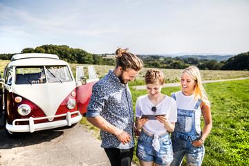 Happy friends outside van in rural landscape looking at tablet