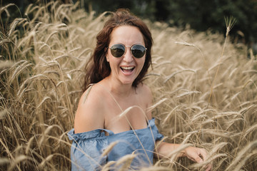 Portrait of happy woman wearing sunglasses in wheat field