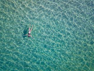 Indonesia, Bali, Melasti, Aerial view of Karma Kandara beach, woman floating on water