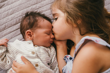Affectionate girl lying on blanket cuddling with her baby brother