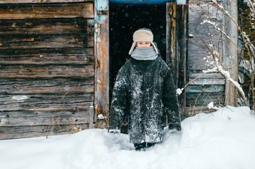 Kids country fashion. Little lovely girl wearing funny oversized clothes. Lifestyle portrait of happy cheerful female kid standing near  house. Comic child in adult winter jacket standing in snowdrift