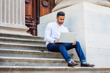 Young East Indian American College Student with beard studying in New York, wearing white shirt, blue pants, leather shoes, sitting on stairs outside office building, working on laptop computer..