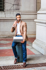 Way to Success, Young East Indian American Man with beard traveling, working in New York City, wearing brown blazer, sitting on pillar on old street, working on laptop computer, talking on cell phone